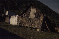 Costruzione d'annata del villaggio sul pendio di collina Grandi montagne di Caucaso alla notte alla luce di luna piena Natura del Fotografie Stock