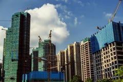 Costruzione dei grattacieli su un fondo di chiaro cielo Fotografie Stock Libere da Diritti