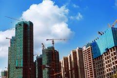 Costruzione dei grattacieli su un fondo di chiaro cielo Fotografia Stock