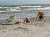 Costruzione del castello di sabbia su una spiaggia Immagini Stock Libere da Diritti