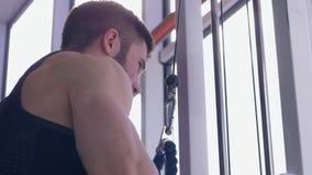 Costruzione del muscolo, maschio di sport che fa allenamento di potere sul simulatore della trazione mentre lavorando al corpo al video d archivio