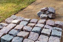 Costruzione del percorso del giardino - porre i lastricatori di pietra del granito fotografie stock libere da diritti