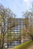 Costruzione dell'alta carica dietro gli alberi Fotografia Stock Libera da Diritti