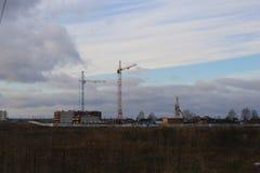 Costruzione dell'edificio residenziale di palazzo multipiano nel campo con l'aiuto di vari alte gru della torre nella stagione di Immagini Stock Libere da Diritti