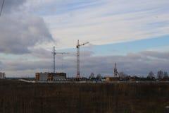 Costruzione dell'edificio residenziale di palazzo multipiano nel campo con l'aiuto di vari alte gru della torre nella stagione di Fotografie Stock