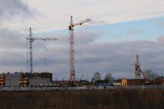 Costruzione dell'edificio residenziale di palazzo multipiano nel campo con l'aiuto di vari alte gru della torre nella stagione di Fotografia Stock Libera da Diritti