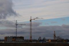 Costruzione dell'edificio residenziale di palazzo multipiano nel campo con l'aiuto di vari alte gru della torre nella stagione di Fotografia Stock