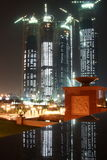 Costruzione dell'orizzonte dell'Abu Dhabi alla notte Fotografia Stock