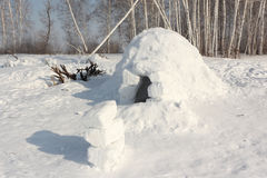 Costruzione della neve un iglù su una radura di inverno Immagini Stock