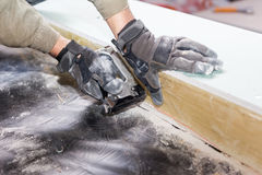 Costruzione della parete della casa di legno Attaccatura del lavoratore una barriera del vapore con la pistola della graffetta Immagine Stock