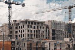 Costruzione delle case di pannello multipiane, grattacielo nella metropoli con le alte gru Costruzione Mosca Fotografie Stock
