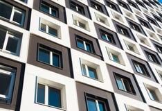 Costruzione di appartamento moderna e nuova Foto di un caseggiato alto con i balconi contro un cielo blu Immagini Stock