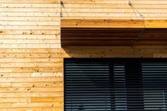 Costruzione di legno con l'architettura moderna della finestra nera immagini stock