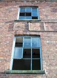 Costruzione di mattone abbandonata di due finestre rotte Immagine Stock