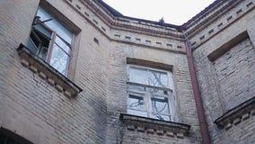 Costruzione di mattone antica con le vecchie finestre e gli uccelli minacciosi che si siedono sul tetto stock footage