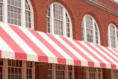Costruzione di mattone con la tenda a strisce Fotografia Stock Libera da Diritti