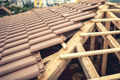 Costruzione di nuova casa, edificio del tetto con le mattonelle marroni e legname Tetto della costruzione dell'appaltatore di nuo Fotografie Stock Libere da Diritti