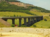Costruzione di nuovo ponte stradale Colonne concrete sopra la piccola valle, grande collina con i miei nel fondo Fotografie Stock