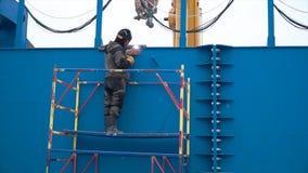 Costruzione di saldatura del sito della struttura d'acciaio del lavoratore clip L'uomo nella maschera fa le strutture di saldatur immagine stock libera da diritti