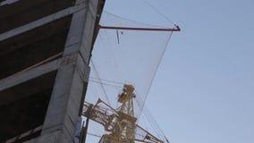 Costruzione di un edificio concreto nella gru a torre del fondo video d archivio