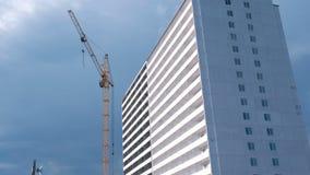 Costruzione di un edificio multipiano Gru di costruzione e della Camera sul fondo del cielo video d archivio