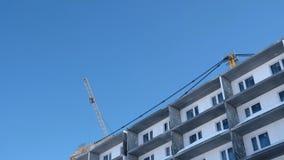 Costruzione di un edificio multipiano La gru si gira verso il lato sopra il tetto archivi video