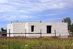 Costruzione di una casa con mattoni a vista bianca fuori di un recinto vicino ad un campo di erba Immagini Stock Libere da Diritti