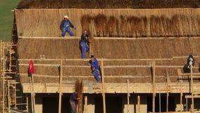 Costruzione di una casa di pesca con il tetto tradizionale ricoperto di paglia video d archivio