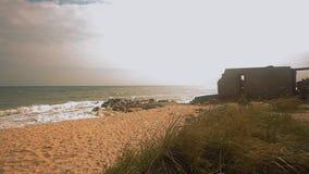 Costruzione dilapidata dal mare, onde nella rottura del mare sulle rocce sul litorale stock footage