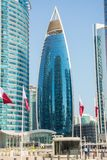 Costruzione in Doha, Qatar della torre di Woqod tra altri grattacieli fotografie stock libere da diritti