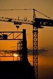 Costruzione e tramonto della gru della siluetta Immagine Stock
