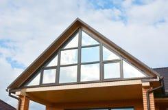 Costruzione moderna della soffitta della casa con guttering del tetto e la mansarda panoramica, finestra del lucernario della sof immagini stock