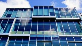 Costruzione, nuvole moderne e cielo blu commerciali riflessi in pannelli di vetro Immagini Stock