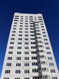Costruzione a più piani Una casa con mattoni a vista alta su fondo blu Immagine Stock Libera da Diritti