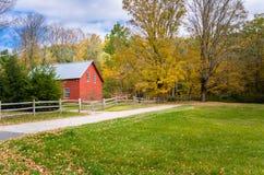 Costruzione rossa in un paesaggio rurale in autunno Fotografia Stock