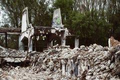 Costruzione rovinata di una fabbrica con calcestruzzo che appende sull'armatura a Fotografie Stock