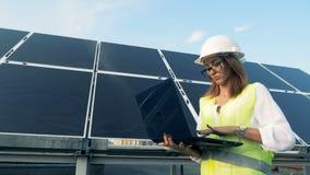 Costruzione solare e giovane una lavoratrice che cammina lungo con un computer portatile Concetto verde di energia video d archivio
