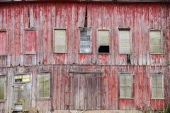 Costruzione stagionata abbandonata con le finestre rotte e la pittura rossa sbiadita Fotografia Stock Libera da Diritti