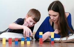 Costruzione torri dai blocchi e dai cubi La mamma ed il figlio che giocano insieme all'istruzione colorata di legno giocano i blo Fotografie Stock