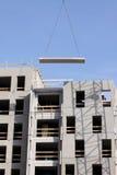 Costruzione urbana moderna in costruzione con la gru e la SK blu fotografia stock