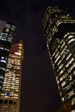 Costruzioni alte alla notte, distretto finanziario moderno, vista del grattacielo di angolo basso, verticale Fotografia Stock