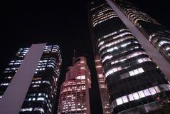 Costruzioni alte del grattacielo alla notte, vista di angolo basso, distretto finanziario del centro Immagine Stock