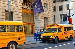Costruzioni, architettura classica, scuolabus giallo con il driver sulla via in Wall Street a Manhattan a New York immagini stock libere da diritti