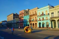 Costruzioni coloniali variopinte con le vecchie automobili d'annata, Avana, Cuba fotografia stock