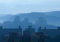Costruzioni d'altezza di aumento di mattina nebbiosa Fotografie Stock Libere da Diritti