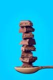 Costruzioni dai cubi dello zucchero e chocololate su un fondo blu Fotografia Stock Libera da Diritti