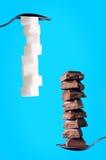 Costruzioni dai cubi dello zucchero e chocololate su un fondo blu Immagine Stock