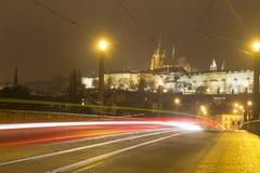 Costruzioni del castello di Praga e st Vitus Cathedral alla notte nell'inverno dall'altro lato di un ponte Immagini Stock Libere da Diritti