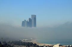 Costruzioni del grattacielo sulla costa circondata da nebbia Fotografia Stock