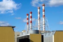 Costruzioni della centrale elettrica con gli alti tubi del fumo Fotografia Stock